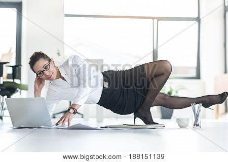Cheerful female secretary having job and resting at same time in modern office. She is using laptop