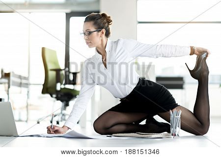 Side view serious woman writing documents while making exercises in modern apartment. She feels tired of feet from long sitting