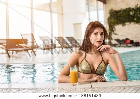 Beautiful woman in a pool in wellness spa hotel resort with a cocktail next to her
