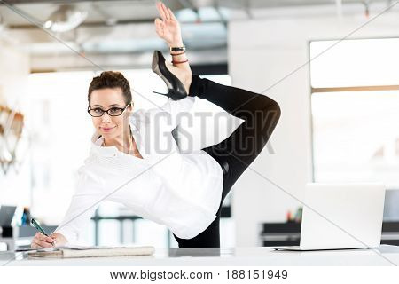 Portrait of smiling female secretary writing documents while making gymnastic exercise in cozy office