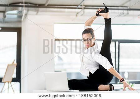 Woman expressing calmness while doing physical work. Shes looking at notebook computer. Rest concept