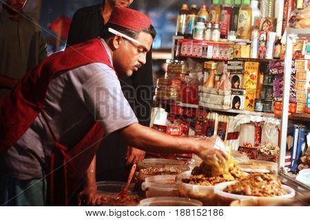 Sales man wearing sindhi hat selling achaar at saddar bazar karachi Pakistan 15/03/2013