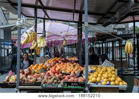 BELGRADE SERBIA - MAY 25 2017: Women selling fruits (mainly lemons and banana) on a stand on Bajlonijeva Pijaca Market in Belgrade near Skadarlija