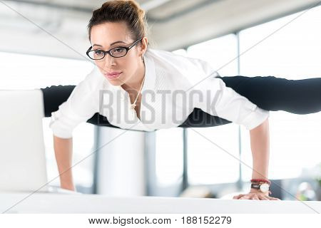Female demonstrating tranquility while working at notebook computer in modern apartment. She has good flexibility