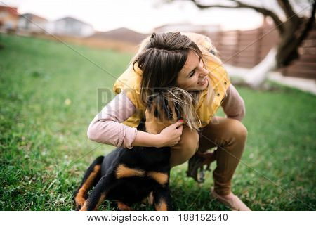 Trendy Hipster Girl Playing And Hugging A Rottweiler Puppy. Woman Playing Fetch With Ball And Dog