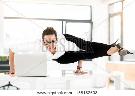 Portrait of cheerful secretary in yoga posture having job in comfortable office. She watching at camera while standing on hands on desk