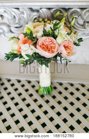 Bridal bouquet of different flowers wrapped lace ribbon near the white white vintage wal on the white wooden floor