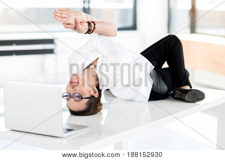 Serene woman watching at notebook computer while locating on desk in apartment. She doing yoga exercise