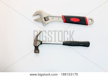 Adjustable Wrenches and hammers on a white backgrounds
