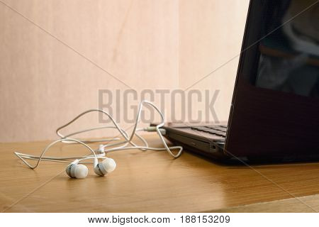 Earphones white listen to music from notebooks put on a wooden background