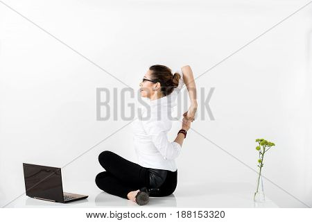Side view smiling female doing exercise for back while working at laptop. Copy space
