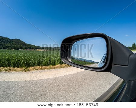 view from car road and side mirror good sunny weather