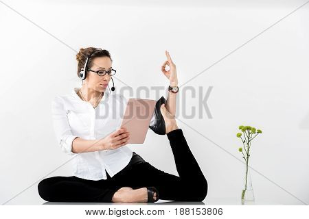 Cheerful female secretary having balance between job and life. She telling by headset while looking at electronic laptop. Copy space