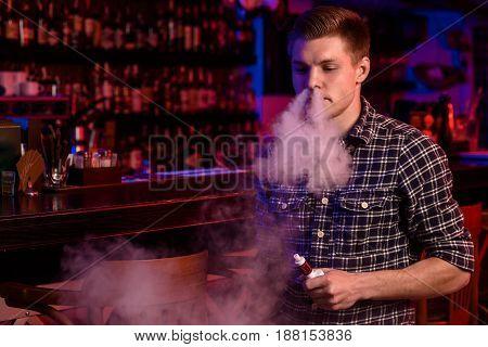 The man smoke an electronic cigarette at the vape shop. Vape bar.