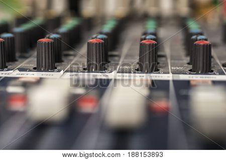 Close up shot of a professional audio mixing console with faders