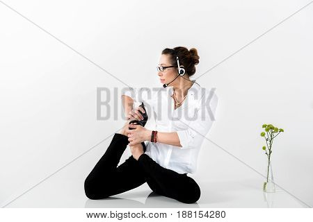 Side view serious female kneading feet during job. She speaking by earphones. Copy space
