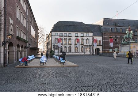 DUESSELDORF, GERMANY - FEBRUARY 13, 2017: Unidentified pedestrants walk acrosss the old market in the Altstadt with and admire the new shining benches.