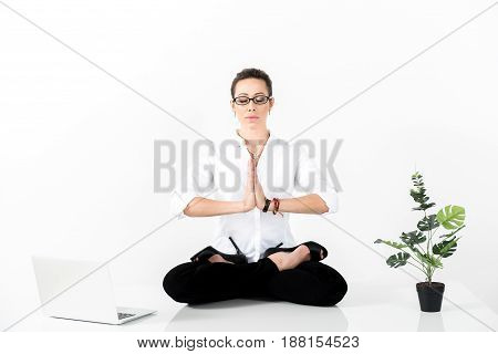 Serious female doing meditation while working with notebook computer. Relaxation concept. Copy space