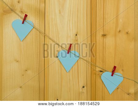 Three hearts with red clothes pegs on a cord on wood