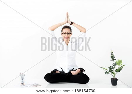 Portrait of smiling lady making meditation during work. She looking at camera. Copy space