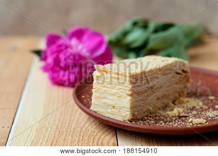 Napoleon's layered cake on a light wooden table in a clay dish with a peony flower.