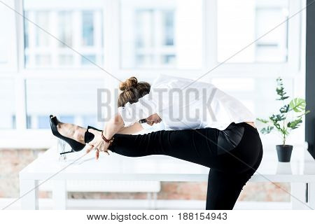 Serious female secretary stretching legs at work. She leaning on table in light office