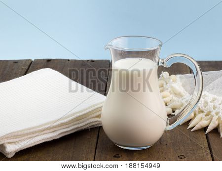 Natural whole milk in glass jug on rustic wooden table with vintage milk jug lace and crochet cover with shells beaded edge - Milk in jug background with space for text