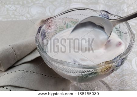Natural greek yoghurt with berries mixed in lovely glass bowel with napkin - Food background with creamy yoghurt on spoon