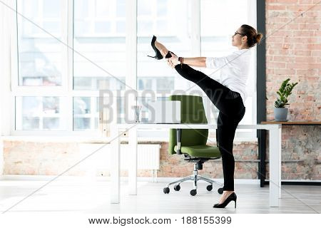 Side view happy woman making exercise during working day in bright office
