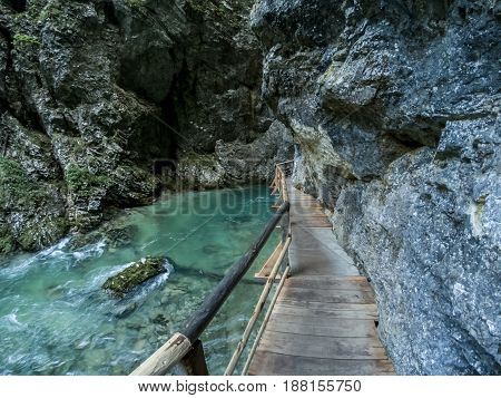 Vintgar canyon water stream and wooden path between rocks