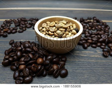 Unroasted coffee beans in a wooden cup and roasted coffee beans on the dark wooden table