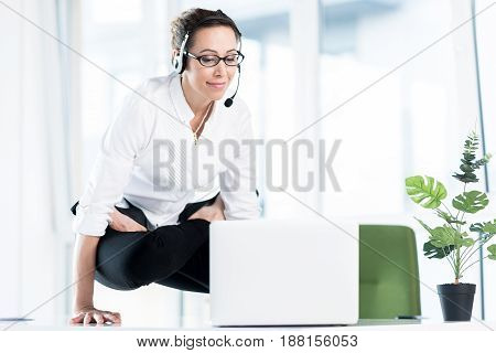 Cheerful woman watching at notebook computer while standing on table by hands. yoga at work concept