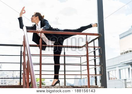 Side view smiling female expressing tranquility while gesturing by hands and doing yoga. She standing on balcony