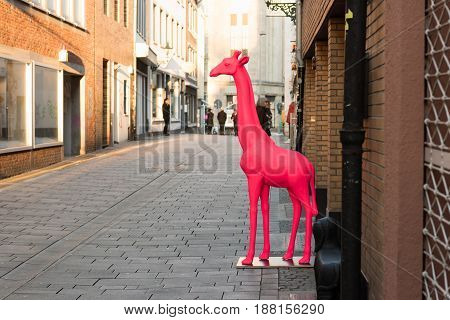 DUESSELDORF, GERMANY - FEBRUARY 13, 2017: With a red giraffe a retailer in the Altstadt increases visibility of his retail store.