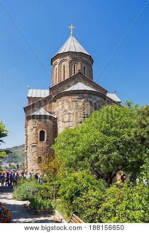 TBILISI GEORGIA - May 1 2017. Tourists near Metekhi Church of the Dormition of the virgin. Famous landmark in Tbilisi Georgia.