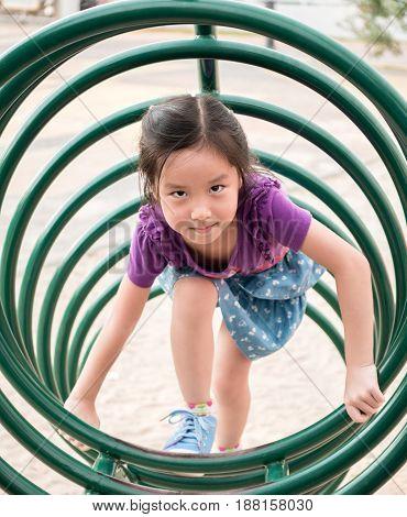 Happy kid asian baby child playing on playground climb the playground equipment circle shape