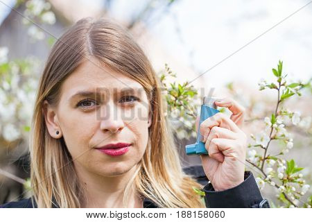 Picture of a young woman having pollen allergy holding a bronchodilator outdoor
