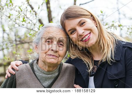 Picture of an elderly woman with cheerful caregiver outdoor in the garden springtime