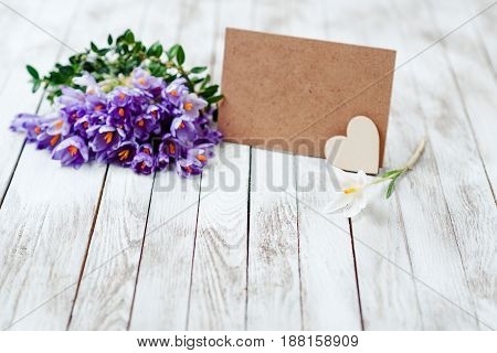 Beautiful crocus flowers in a basket near empty card for your text on the wooden background.