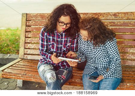 Two young women with phone and a tablet computer outdoors. Toned.
