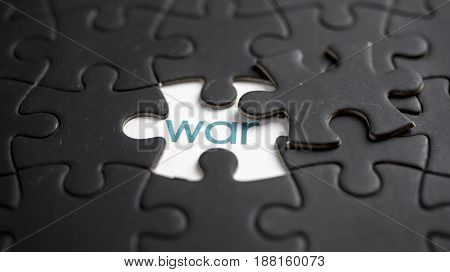 Word war under black jigsaw puzzle piece