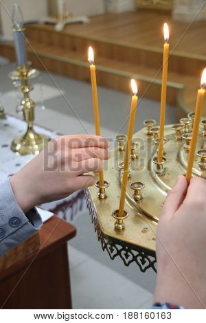 Boy in church puts a candle and pray