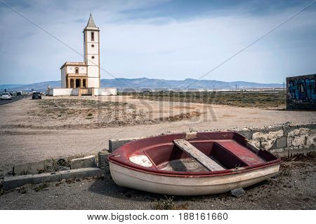 San Miguel Beach and Salinas church with stranded boats take in Cabo de gata Almeria Andalusia Spain