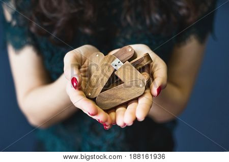 Cute girl with dark hair holding a wooden flash drive on a blue background. Close-up
