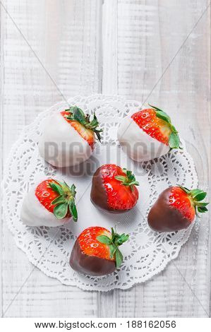 Fresh strawberries dipped in dark and white chocolate on light background close up. Delicious dessert and candy bar. Top view