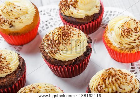 Tasty cupcakes with candies and chocolate on light background close up.