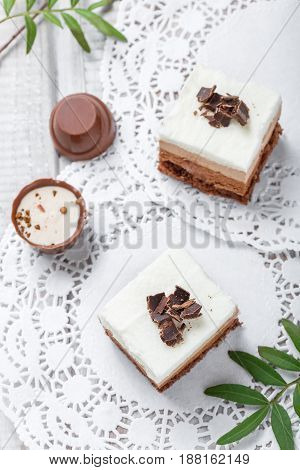 Mini cakes with white chocolate cocoa and candies on light background close up.