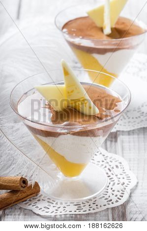 Tasty fruit mousse dessert with white chocolate in a glass on light background close up. Delicious dessert and candy bar. Top view