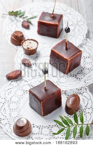 Chocolate souffle candy dessert with chocolate praline and cocoa beans on wooden background close up. Top view.