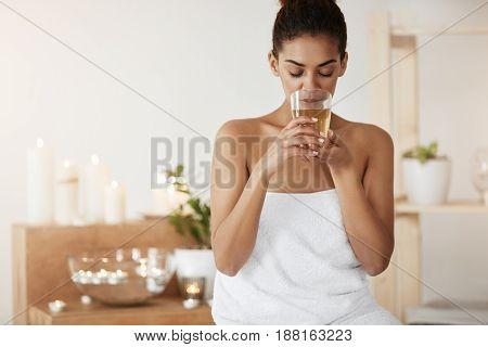 Tender african girl in towel drinking green tea resting in spa salon.
